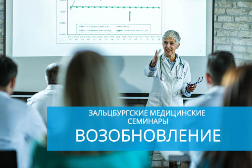 Happy mature female doctor talking to large group of her colleagues on a presentation in a hospital.