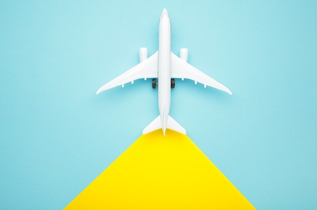 model-airplane-on-yellow-and-blue-background-travel-concept_106006-5004